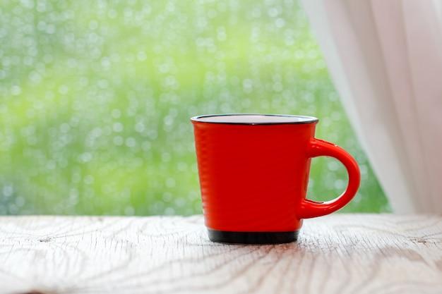 Caneca de café vermelho na mesa de madeira e janela de gota de chuva