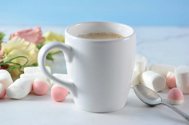 Caneca de cappuccino em branco com flores e marshmallow