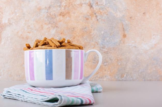 Caneca de cerâmica com saborosos biscoitos crocantes em fundo de mármore. foto de alta qualidade
