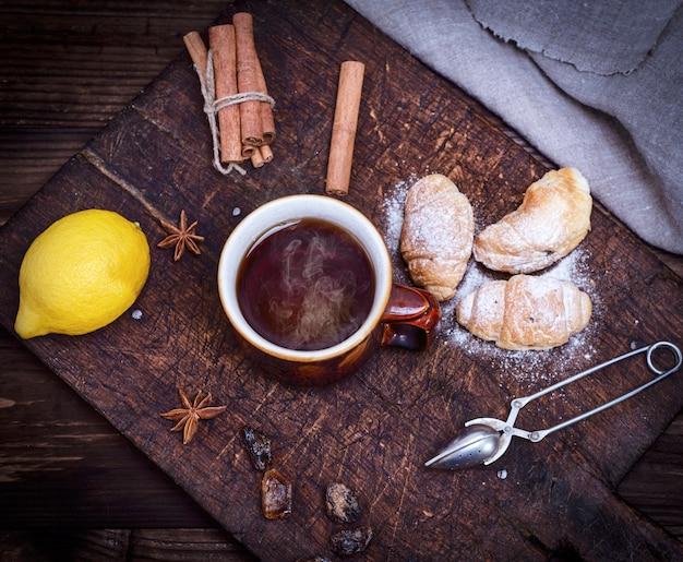 Caneca de cerâmica marrom com chá preto quente