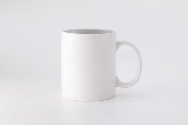 Caneca de cerâmica no fundo branco. copo de bebida em branco para seu projeto.
