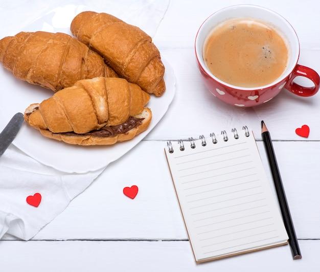 Caneca de cerâmica vermelha com café quente e croissants frescos