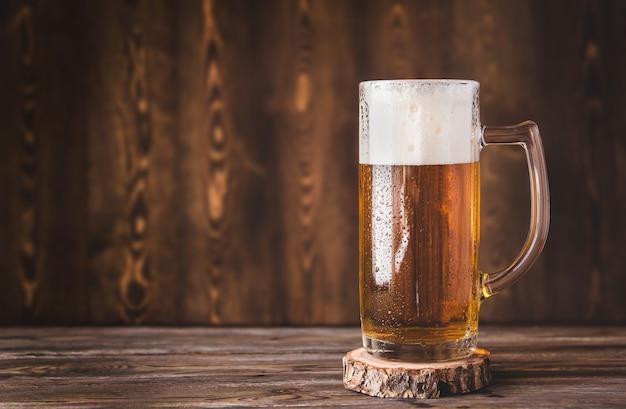 Caneca de cerveja com espuma em uma mesa de madeira