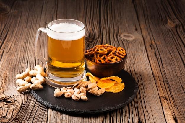 Caneca de cerveja com pistache e lanches na placa de madeira