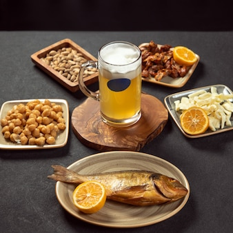 Caneca de cerveja com salgadinhos de peixe grelhado, ervilha e queijo