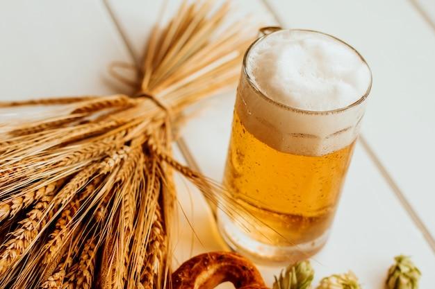 Caneca de cerveja, cones de lúpulo, espigas de centeio e trigo e pretzels em madeira branca