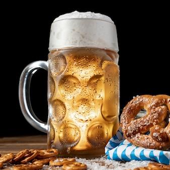 Caneca de cerveja de close-up com espuma e pretzels
