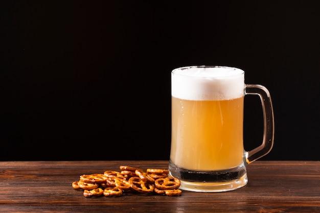 Caneca de cerveja de close-up com pretzels