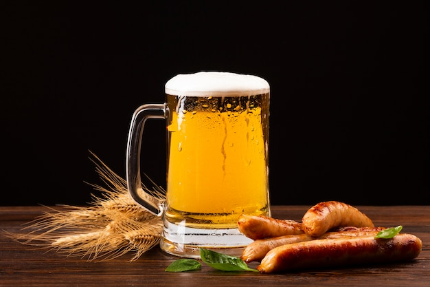 Caneca de cerveja de close-up com salsichas