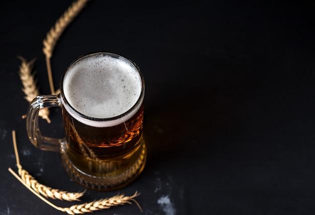 Caneca de cerveja de vidro em uma mesa escura