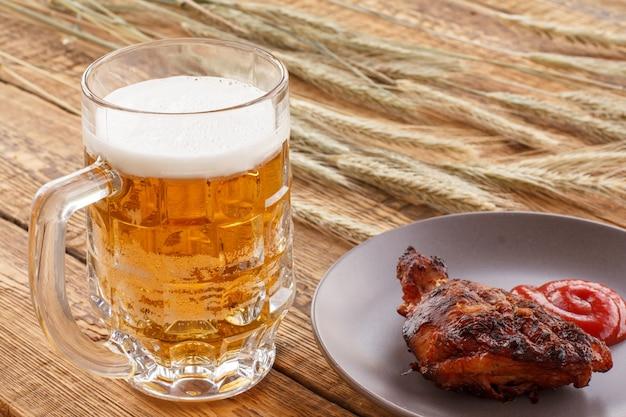 Caneca de cerveja de vidro, prato com frango grelhado e molho de tomate, espigas de cevada em um fundo de madeira.