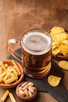 Caneca de cerveja deliciosa de ângulo alto e batatas fritas