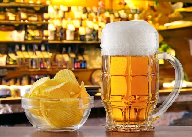 Caneca de cerveja e batatas fritas na mesa no bar