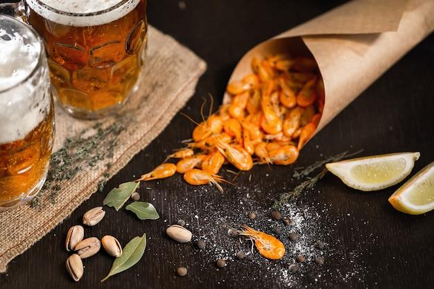 Caneca de cerveja e camarão grelhado na mesa de madeira