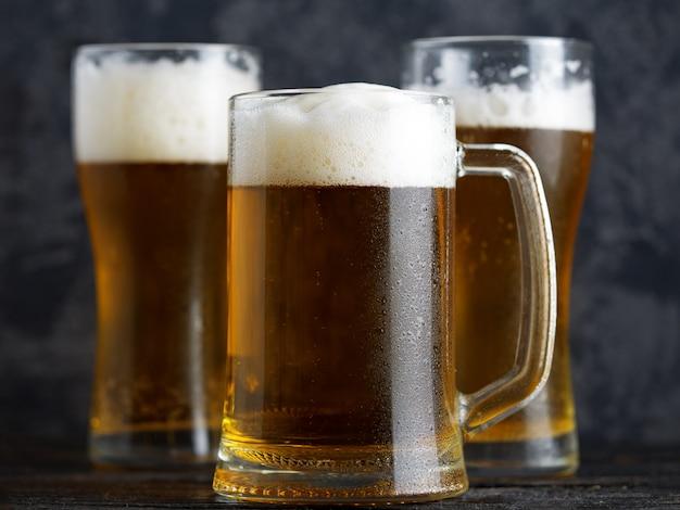 Caneca de cerveja e copos de cerveja em um plano de fundo escuro