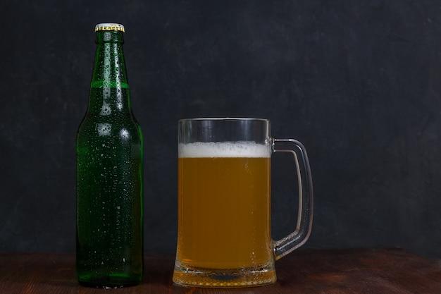 Caneca de cerveja e garrafa verde com cerveja na mesa de madeira no escuro b