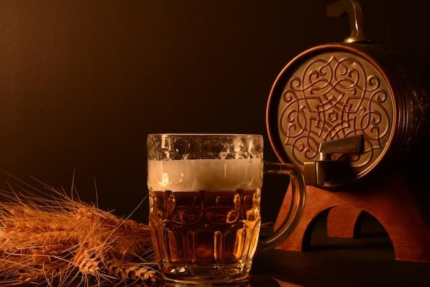 Caneca de cerveja e trigo e peixe seco em fundo escuro