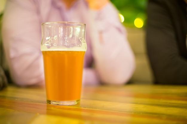 Caneca de cerveja em cima da mesa no fundo de um homem em uma camisa
