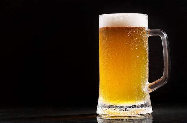 Caneca de cerveja gelada em fundo escuro