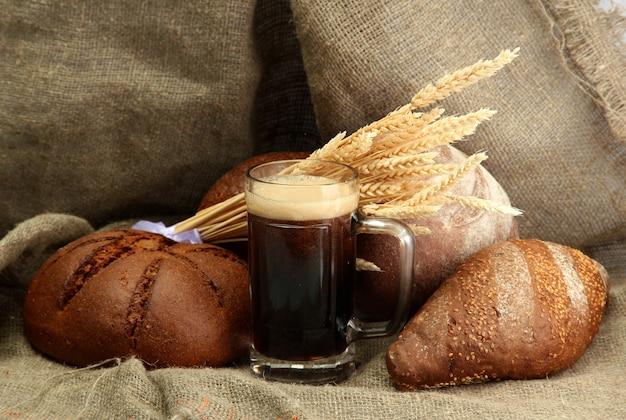 Caneca de cerveja kvass e pão de centeio com espigas, sobre fundo de serapilheira