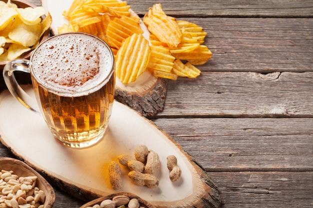 Caneca de cerveja lager e lanches na mesa de madeira