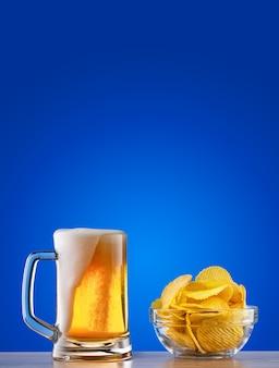 Caneca de cerveja light com espuma e batatas fritas no fundo azul