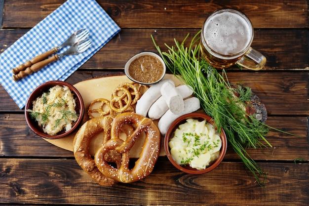 Caneca de cerveja, pretzels e salsichas na mesa de madeira. vista do topo