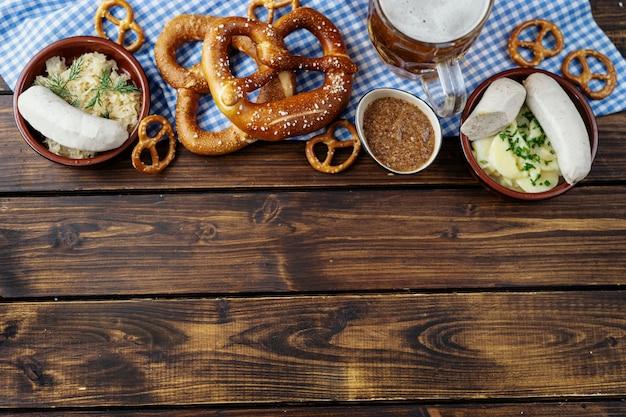 Caneca de cerveja, pretzels e salsichas no fundo da mesa de madeira em vista superior