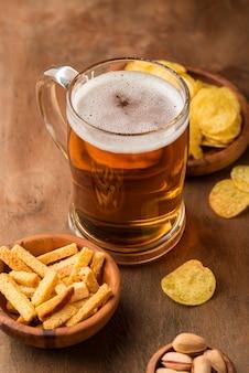 Caneca de cerveja saborosa de ângulo alto e batatas fritas