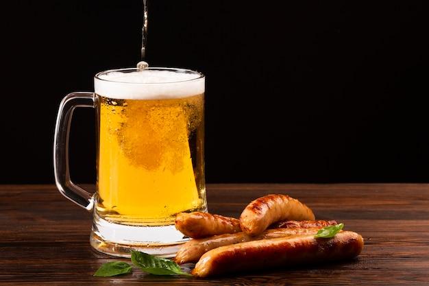 Caneca de cerveja vista frontal com salsichas
