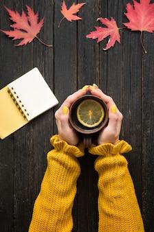 Caneca de chá com limão em uma mão feminina, lápis e bloco de notas.