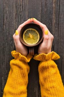 Caneca de chá com limão em uma mão feminina.