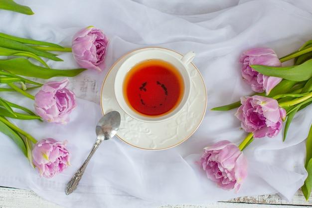 Caneca de chá de natureza morta e buquê de tulipas em tecido branco