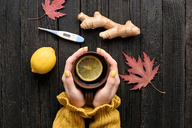 Caneca de chá nas mãos femininas com limão, gengibre e termômetro