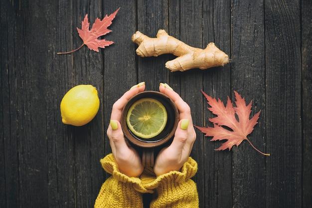 Caneca de chá nas mãos femininas. limão, gengibre e folhas de outono. tratamento a frio. vista do topo