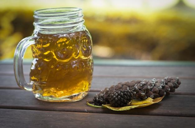 Caneca de chá ou café e cone no fundo de madeira, ao ar livre, conceito de outono