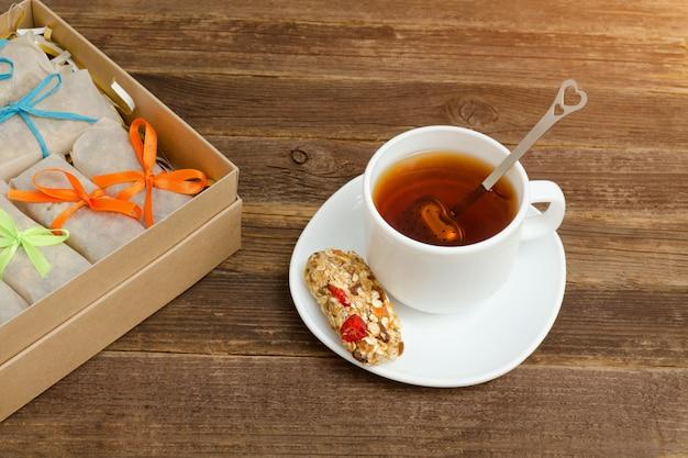Caneca de chá preto, uma barra de cereais e caixas com barras
