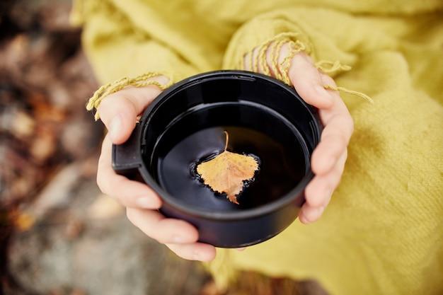 Caneca de chá quente na mão da mulher é outono em uma floresta