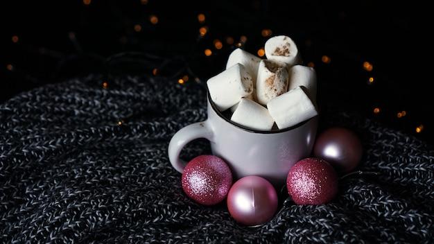 Caneca de chocolate quente com marshmallow em um fundo escuro, bebida quente de natal de inverno com bolas de natal cor de rosa