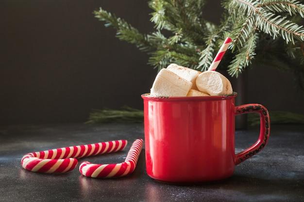 Caneca de chocolate quente com marshmallows e galhos de árvores de natal em preto