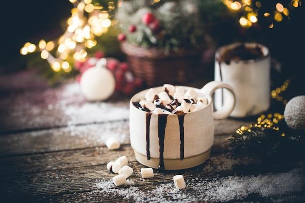 Caneca de chocolate quente com marshmallows no fundo da decoração de natal