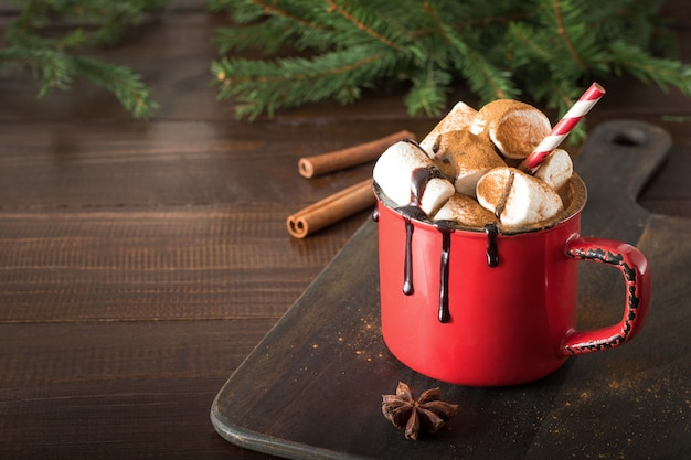 Caneca de chocolate quente e cacau com marshmallows com galhos de árvore de natal na placa de madeira. feriado de natal.