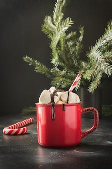Caneca de chocolate quente e café com marshmallows com galhos de árvores de natal em preto