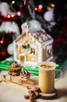 Caneca de close-up com café e leite em uma mesa de madeira, casa de gengibre e luzes de natal e decorações em bokeh