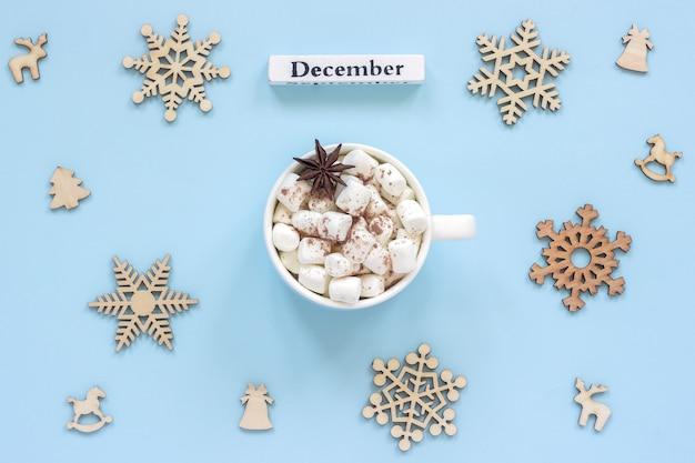 Caneca de dezembro do calendário marshmallows de cacau e grandes flocos de neve de madeira