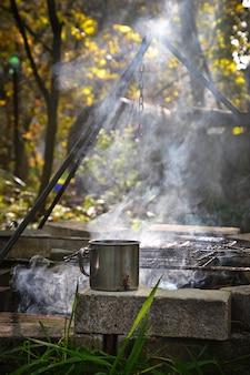 Caneca de ferro com bebida quente perto de fogo