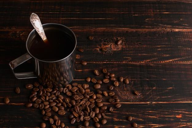 Caneca de ferro com café preto e grãos de café em uma mesa de madeira. copyspace.
