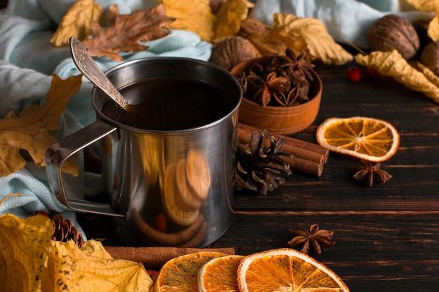 Caneca de ferro com café preto, especiarias, laranjas secas, sobre um fundo de um cachecol, folhas secas em uma mesa de madeira. clima de outono, uma bebida quente. copyspace.