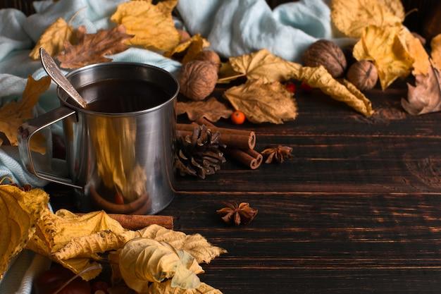 Caneca de ferro com café preto, especiarias, sobre um fundo de um cachecol, folhas secas em uma mesa de madeira. clima de outono, uma bebida quente. copyspace.
