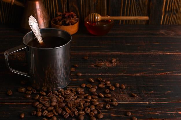 Caneca de ferro com café preto, mel e grãos de café em uma mesa de madeira. copyspace.